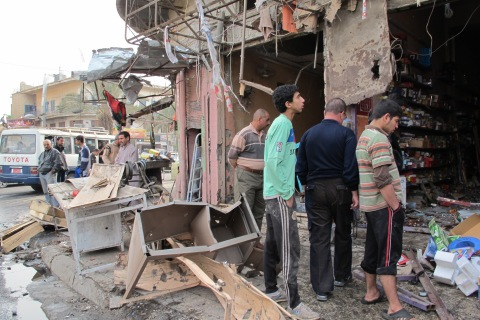 Iraqis inspect the damage after a wave o