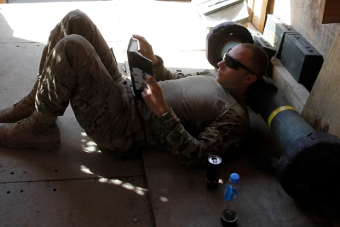 A soldier from 3rd Platoon, 2-27 Infantry uses a Javelin rocket as a pillow while reading a book in Outpost Bari Alai in Ghaziabad district in Kunar, Afghanistan.