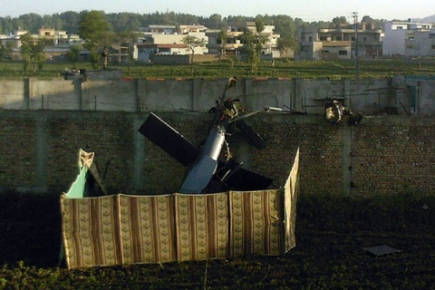 The tail of a crashed American helicopter sits beside the wall of the compound where Osama bin Laden hid until he was killed in a raid on May 2, 2011.