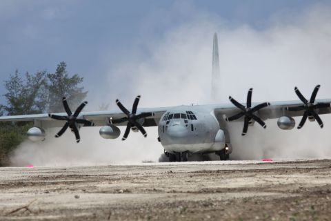 """A Marine Corps C-130 touches down on Tinian Island's North Field, Wednesday, May 30 – the first aircraft to land there since 1947. North Field was once the largest airfield in the Pacific and was the launching point for the atom bomb raids on Hiroshima and Nagasaki during World War II. Marine Aircraft Group-12 cleared and repaired runway Baker of jungle and undergrowth as part of a month-long expeditionary training exercise. The US and Japan are surveying sites on Tinian and elsewhere in the Northern Mariana chain for potential joint-training bases – part of the US """"pivot"""" to the Asia-Pacific region.  USMC PHOTO"""