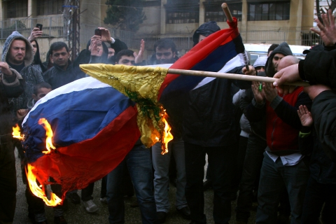 Demonstrators burn a Russian flag and th