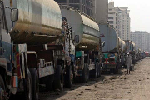 A pakistani man walks past fuel tanker t