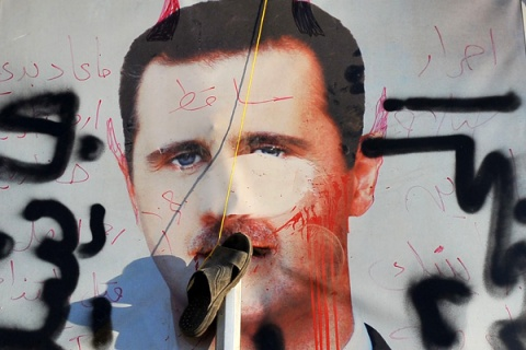 A slipper hangs on a vandalised poster of Syrian President Bashar al-Assad lying in a trash container in the northern city of Aleppo on July 24, 2012.