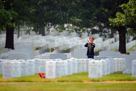 Taps are played by an Army bugler at a soldier's burial in Arlington Cemetery on June 21 2012