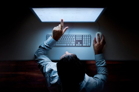 Man points at glowing computer screen in darkness