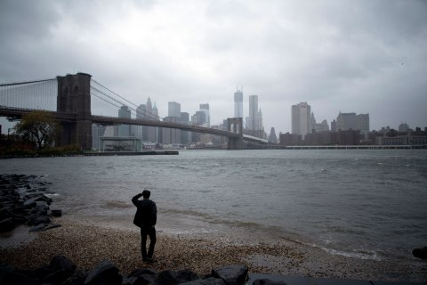 A man watches rising waters on the East River from Brooklyn as Hurricane Sandy made its approach in New York, on Oct. 29, 2012.