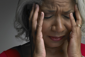 Mature woman with head in hands and eyes closed