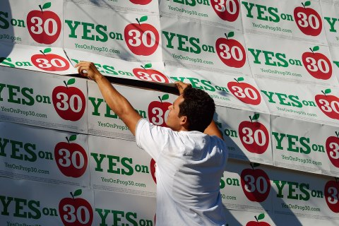 image: A volunteer covers a wall of a mini-mall with Proposition 30 placards before a rally in Panorama City, Calif., Nov. 5, 2012.
