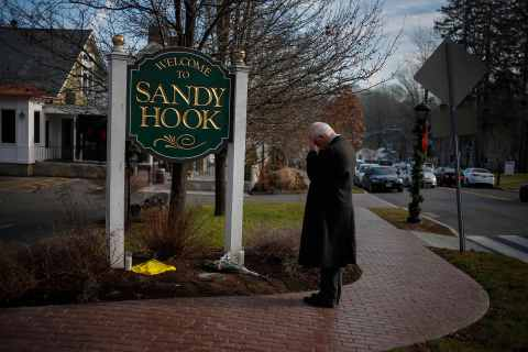 image: New Jersey resident Steve Wruble, who was moved to drive out to Connecticut to support local residents, grieves for victims of an elementary school mass shooting at the entrance to Sandy Hook village in Newtown, Conn., on Dec. 15, 2012.