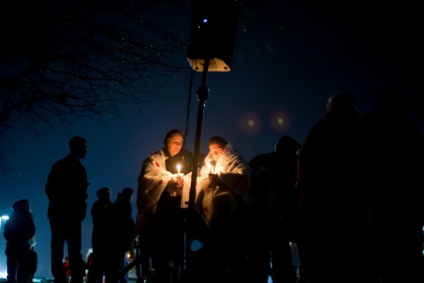 image: Mourners listen to a memorial service over a loudspeaker outside Newtown High School for the victims of the Sandy Hook Elementary School shooting in Newtown, Conn., Dec. 16, 2012.