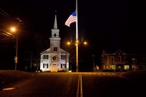 image: A flag flies at half-staff on Main Street in Newtown, Conn., on Saturday, Dec. 15 2012.