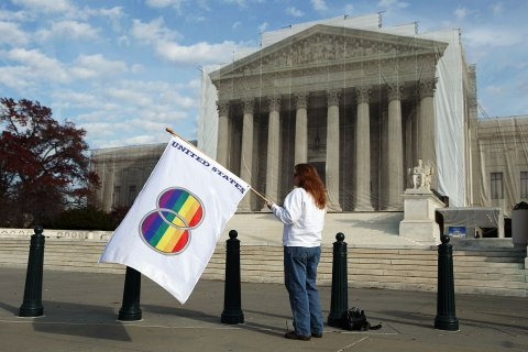 image: Same-sex marriage proponent Kat McGuckin of Oaklyn, N.J., holds a gay pride flag while standing in front of the Supreme Court in Washington, Nov. 30, 2012.