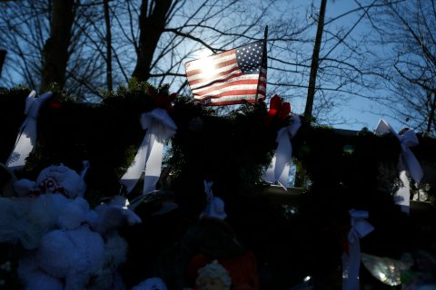 A flag that bears the names of the dead flies over a makeshift memorial in Sandy Hook, after the Dec. 14 shooting tragedy when a gunman shot dead 20 students and six adults at Sandy Hook Elementary, in Newtown, Conn., on Dec. 28, 2012.