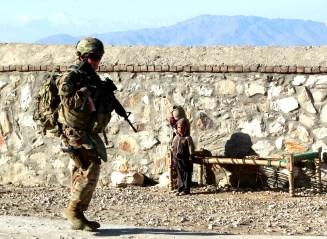 Children look at a female U.S. soldier on patrol in Pachir wa Agam in Nangarhar
