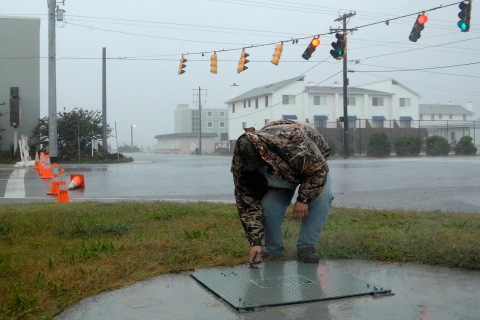 An employee from the sewer authority check pumps meant to keep rising sea water from clogging the system as Hurricane Sandy bears down on Dewey Beach