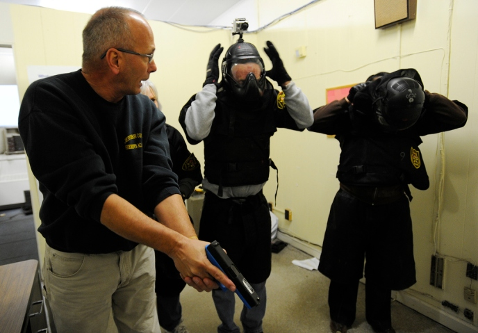 image: During a school-shooter training session in Birmingham, Ala., administrators put on protective gear as Jefferson County Sheriff's Deputy Greg Reeves shows them how to enter a classroom with a pistol on Jan. 2, 2013.