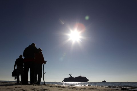 People on Spanish Fort watch as a disabled Carnival Lines cruise ship is towed to harbor off Mobile Bay, Ala., Feb. 14, 2013.