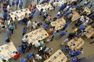 Employees and customers are seen during the official opening of the largest Apple shop in southern Europe, at Passeig de Gracia in Barcelona