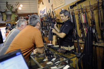 A gun shop owner shows his last two AR-15 style rifles to a group of customers in Sarasota