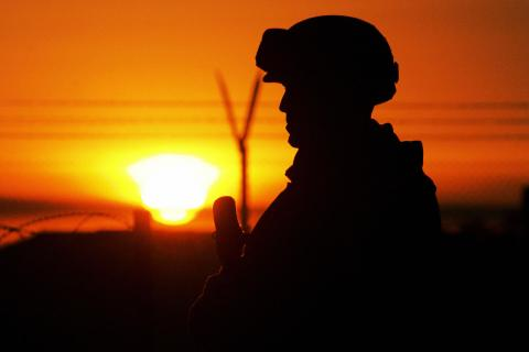 The sunrise is seen behind a US marine i