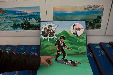 A North Korean teacher holds open a children's pop-up book, which depicts a U.S. soldier killing a Korean woman with a hatchet, in a library room at Kaeson Kindergarten in central Pyongyang.