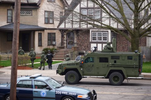Police and SWAT teams search neighborhoods yard by yard in Watertown, Mass., on 19 April 2013.
