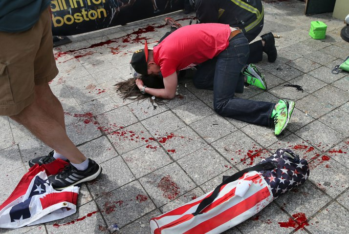 A man comforts a victim on the sidewalk at the scene of the first explosion near the finish line of the 117th Boston Marathon, April 15, 2013.