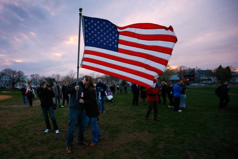 Neighbors hug under a U.S. flag as they arrive for a candlelight vigil in the Dorchester neighborhood of Boston