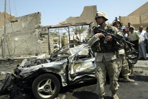 A US soldier guards a car which exploded
