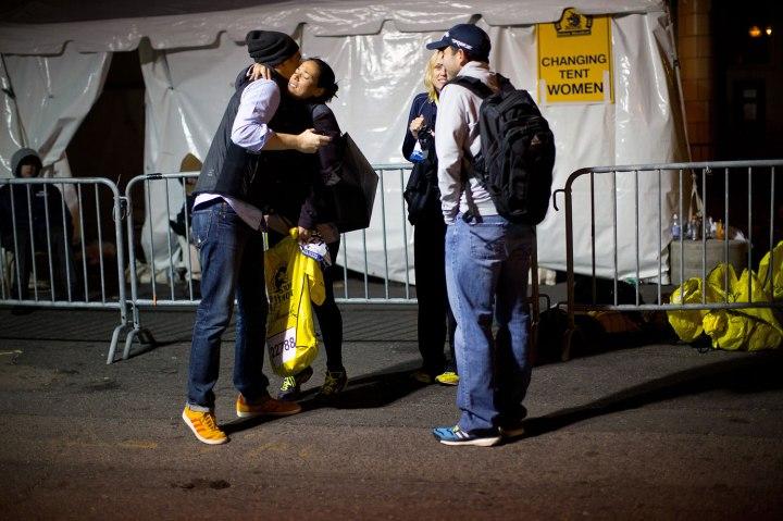 Sheila Eslinger, a Boston Marathon runner, hugs a man after picking up her belongings late Monday night.