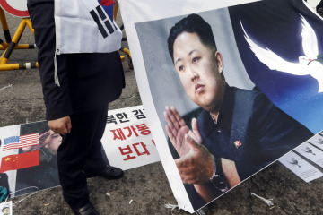 A protester holds a sign showing a portrait of North Korean leader Kim Jong-Un as a portrait of South Korean President Park Geun-hye is seen on the ground during an anti-North Korean protest in Paju