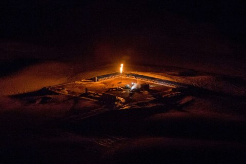 An aerial image shows a natural gas flare after sunset outside of Williston