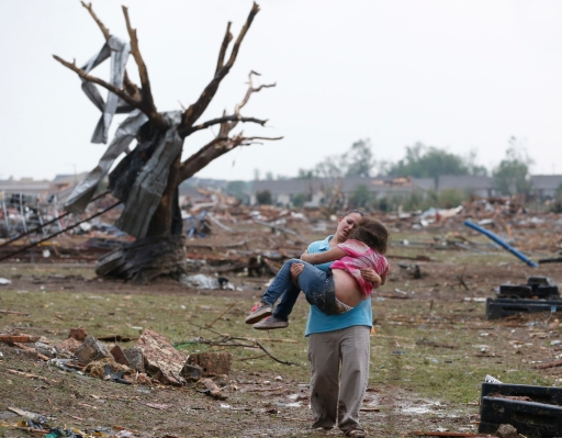 A woman carries her child through a field near the collapsed Plaza Towers Elementary School in Moore, Okla., May 20, 2013.