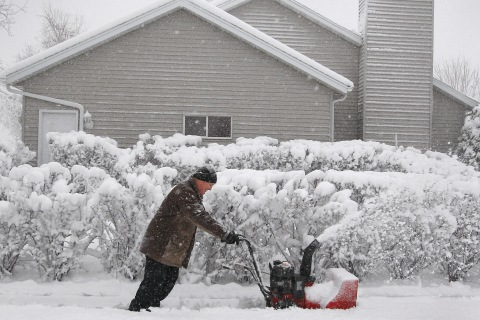 Tarrance Harms pushes on his snow-blower as it struggles to clear the heavy snow off his northeast Rochester, Minn., on May 2, 2013.
