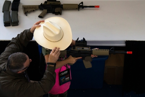 A man adjusts a girl's hat before she takes aim with an airsoft gun during the NRA Youth Day at the National Rifle Association's annual meeting in Houston, Texas
