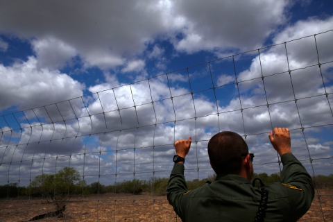A U.S. Border Patrol agent looks out at the desert near Falfurrias, Texas