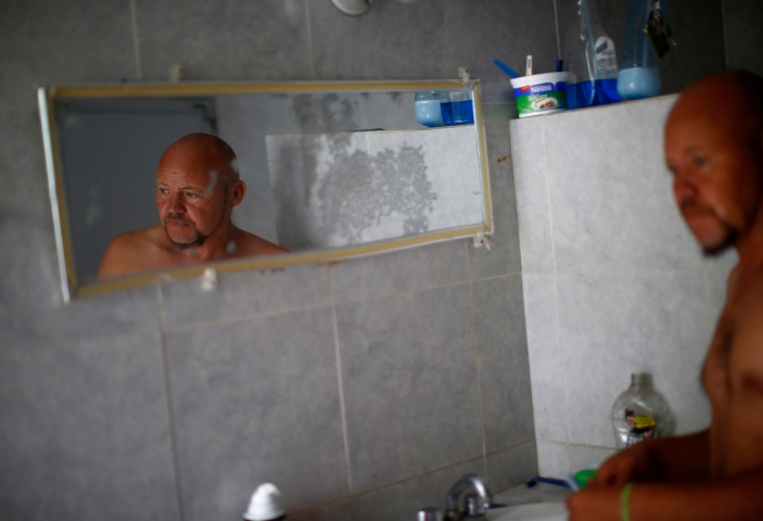 A man is reflected in a mirror at Casa del Migrante in Reynosa, Mexico