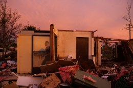 Jason Owen walks past an open door as he helps his mother to salvage items from her uncle's home after it was almost destroyed by a tornado in Moore, Oklahoma, May 23, 2013.