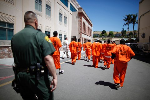 Inmates are escorted by a guard through San Quentin state prison in San Quentin, Calif., on June 8, 2012.