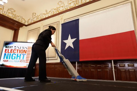 Marta Rangel Medel vacuums the stage in preparation for the Texas Democratic Party election watch party, in Austin, Nov. 6, 2012. Attorney General Eric Holder says Texas is the first place that he will intervene to defend against what he calls attacks on the voting rights of minorities,