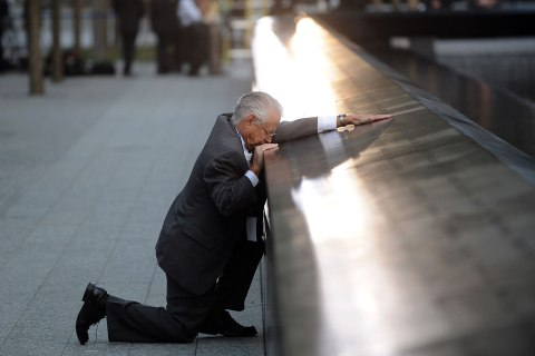 Robert Peraza, who lost his son Robert David Peraza, pauses at his son's name at the North Pool of the 9/11 Memorial during tenth anniversary ceremonies at the site of the World Trade Center in New York, Sept. 11, 2011.