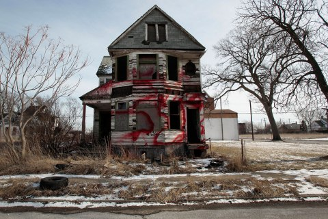 A vacant and blighted home, covered with red spray paint, sits alone in an east side neighborhood once full of homes in Detroit, Jan. 27, 2013.