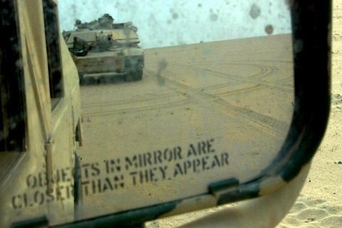 U.S. ARMY ABRAMS TANK APPEARS IN REAR VIEW MIRROR IN KUWAIT DESERT.