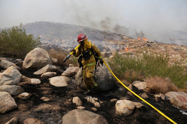 A firefighter works to keep the fire from spreading as the Silver Fire moves into the foothills above Ida Avenue in Cabazon, California