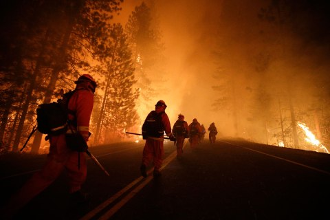 Inmate firefighters walk along state Highway 120 as firefighters continue to battle the Rim Fire near Yosemite National Park, Calif., Aug. 25, 2013.