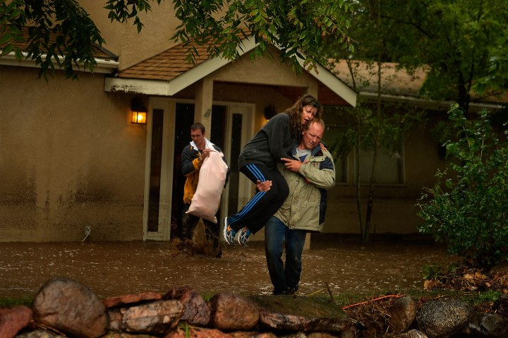 Kyle Schuler carries his wife Cheryl from their home after salvaging what they in Boulder, Colo., September 12, 2013.