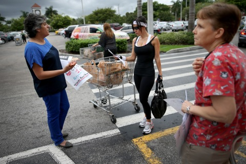 From left: Jessy Abouarab talks with Excelina Ordonez about the Affordable Care Act, the benefits of health coverage and the new health care options outside a grocery store in Miami, on Sept. 16, 2013 in Miami, Florida.
