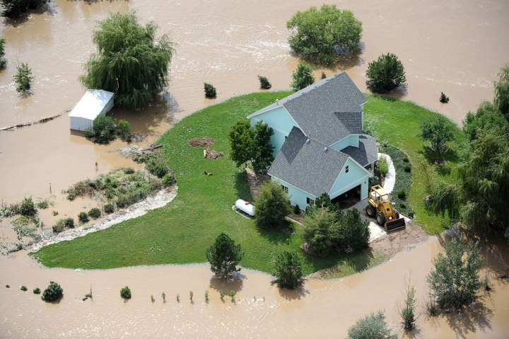 A home near Evans, Colo.,  is surrounded by flood waters from the South Platte River, on Sept. 16, 2013.