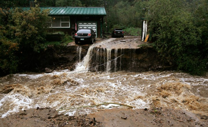 A home and car are stranded after a flash flood in Coal Creek destroyed the bridge near Golden, Colo., September 12, 2013.
