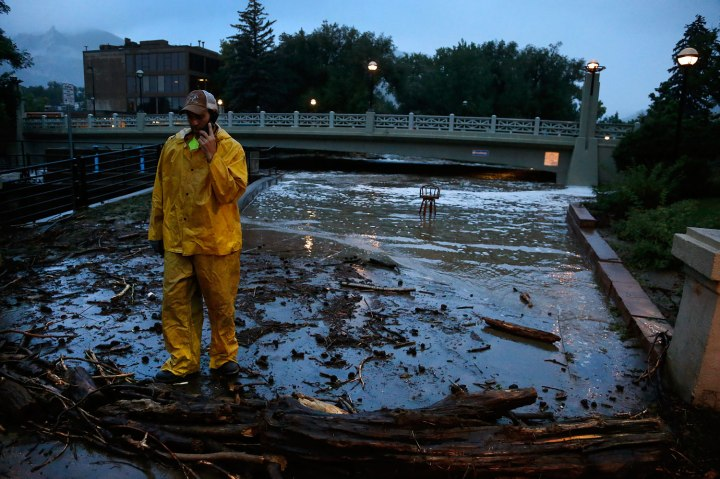 A city worker talks on his phone while surveying high water levels on Boulder Creek following overnight flash flooding in downtown Boulder, Colo., on Sept. 12, 2013.